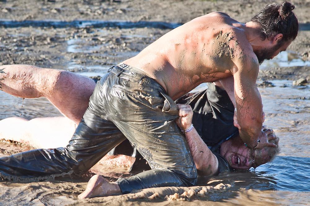 Men wrestling in mud hole, Ninilchik, Alaska