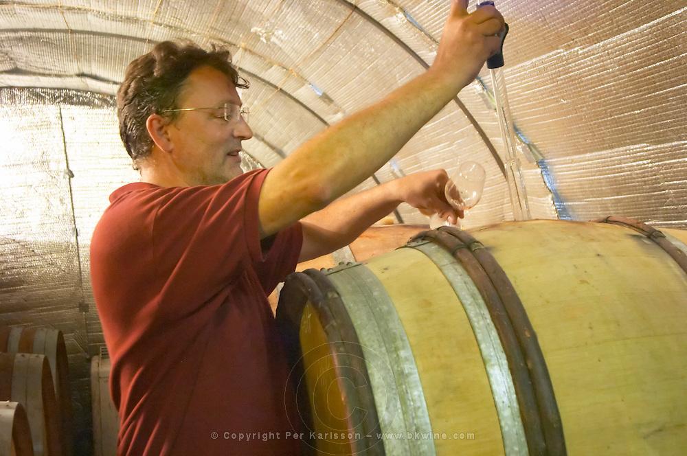 Daniel Le Conte des Floris Domaine Le Conte des Floris, Caux. Pezenas region. Languedoc. Barrel cellar. Drawing a sample with a pipette. Owner winemaker. France. Europe.