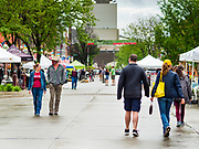 23 MAY 2020 - AMES, IOWA: Shoppers, many wearing face masks, walk through the Farmers' Market in downtown Ames. The Ames Main Street Farmers' Market reopened Saturday after nearly a month of only online sales because of Iowa's bans on large gatherings caused by the COVID-19 pandemic. Only about 15 venders set up stalls Saturday and attendance was significantly lower than normal. All of the venders wore face masks and many, but not all, of the shoppers wore face masks. Farmers' markets are popular community gatherings in Iowa, but they've been on hiatus since the Coronavirus (SARS-CoV-2) pandemic. At this time, Iowa farmers' markets are not allowed to have entertainment or sell non-food or non-agricultural goods.           PHOTO BY JACK KURTZ