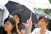 Hmong teens walk among concession tents under sun umbrellas. Hmong Sports Festival McMurray Field St Paul Minnesota USA
