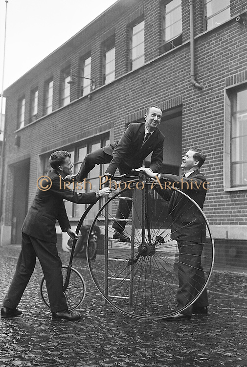 """A 70 year old 'Penny  Farthing' was presented by the Irish Raleigh Cycle Company to the Pioneer Club for use in their pantomime """"Red Riding Hood"""" at the Francis Xavier Hall, Dublin. Mr. John Brierton, who will ride the bicycle on the stage, tries out his mount for the first time.  Helping him are Mr. Harry Doherty, Sales Manager, Irish Raleigh Cycle Company, and Mr. William Rocke, Publicity Officer, Red Riding Hood Pantomime..17.12.1962"""