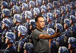 (170730) -- BEIJING, July 30, 2017 (Xinhua) -- A visitor takes a selfie in front of a work displayed in a photo exhibition marking the 90th anniversary of the People's Liberation Army(PLA) in Beijing, capital of China, July 30, 2017.   (Xinhua/Chen Yehua)(clq) (Photo by Xinhua/Sipa USA)