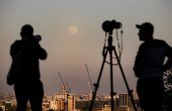 © Licensed to London News Pictures. 06/05/2020. London, UK. People watch as the near full Supermoon rises through the haze over central London. Also know as the Flower Moon at this time of year - it will be at it's fullest as it rises later tomorrow. A supermoon is a full or new moon that comes closest to the Earth in its elliptical orbit—resulting in a slightly larger than usual apparent size when viewed from Earth. Photo credit: Peter Macdiarmid/LNP