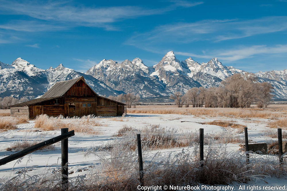 T.A. Moulton barn in the foreground of the Grand Tetons on a cold, mostly clear winter day.