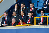 a number of Vincent Tan representatives /Cardiff city directers  inc  front , from left to right Steve Borley (far left), chairman Mehmet Dalman,  Ken Choo, the general manager  (in centre) look on from the grandstand. Skybet football league championship match , Millwall v Cardiff city at the Den in Millwall, London on Saturday 25th October 2014.<br /> pic by John Patrick Fletcher, Andrew Orchard sports photography.