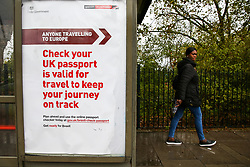 "© Licensed to London News Pictures. 11/10/2019. London, UK. A member of the public walks past the latest Brexit poster advert featuring 'Anyone Travelling to Europe"" displayed at a bus stop in north London, with twenty days to Brexit day. The Get ready for Brexit campaign is costing £100m, preparing the nation to depart the EU. British passport holders are urged to ensure they have at least six months validly on their passports to travel to Europe after Brexit. Passport validity rules will become tighter if there is a no deal. Photo credit: Dinendra Haria/LNP"