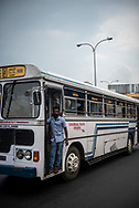 A man working on a public bus stands at the entrance as it travels down a street in Colombo, Sri Lanka.