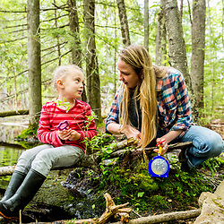 A woman plays with a young girl in the woods at the Orris Falls Preserve in South Berwick, Maine.