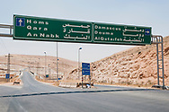 Highway sign in Syria directing traffic to Damascus and other cities, including Homs and Qara.