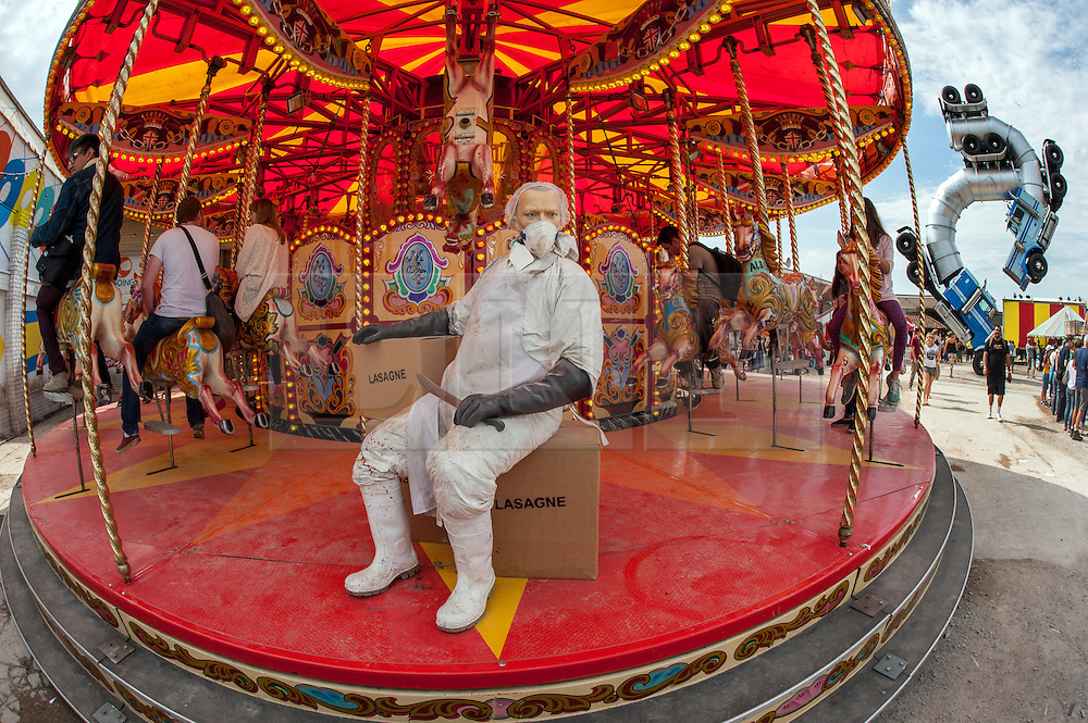 © Licensed to London News Pictures. 22/08/2015. Weston-super-Mare, North Somerset, UK.  A mannequin with a butcher's knife sitting on boxes of lasagne on the fairground horse ride on the first main day of BANKSY's Dismaland show at the old Tropicana on Weston seafront, when the event is open to the general public. Photo credit : Simon Chapman/LNP