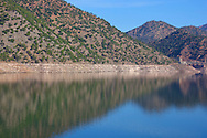 Mountain and tree reflections in the water reservoir Ouirgane in the High Atlas Mountains.