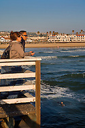 Couple looking out over the water from pier at Pismo Beach, California