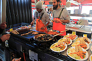 Street stall restaurant cooking fish meals in Torget market, Bergen, Norway