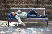 Man (possibly homeless / street drinker) sleeping on a bench in East London.