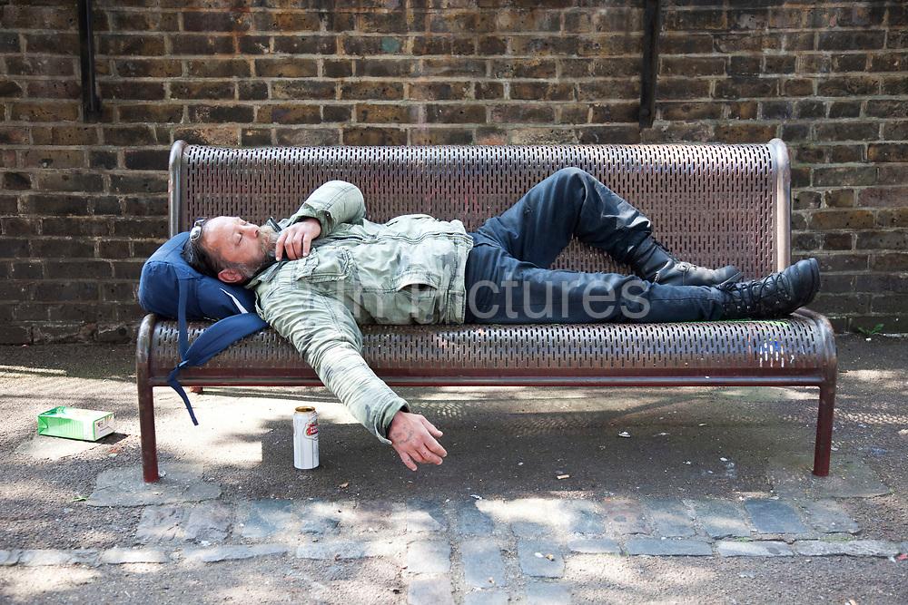 Man (possibly homeless / street drinker) sleeping on a bench in East London.