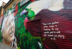 """© Licensed to London News Pictures. 06/05/2019. London, UK.  A woman and her dog walk past a new David Attenborough Mural painted on the side of a house in St Matthew's Row, east London.  The mural by urban artist, Jerome shows natural historian, David Attenborough with a message, """"There is no question climate change is happening. The only arguable point is what part humans are playing in it"""". Photo credit: Vickie Flores/LNP"""