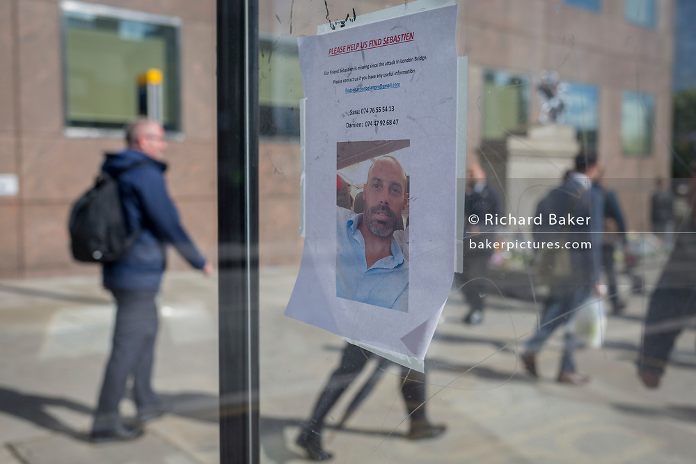 Three days after the terrorist attack in which 7 people died and many others suffered life-changing injuries on London Bridge and Borough Market, the face on a still-missing French citizen Sebastien Belanger appears on a poster at the bus stop near a flower shrine, on 6th June 2017, on London Bridge, in the south London borough of Southwark, England. City commuters now back at work walk respectfully and quietly past the floral memorial at the plinth marking the southern boundary of the City of London, the capital's financial district.