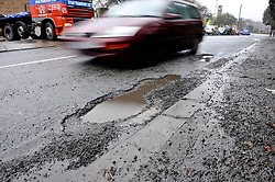 Embargoed to 0001 Tuesday August 1 File photo dated 20/01/10 of a car driving around a pothole. Pothole-related breakdowns soared by almost a third between April and June compared with the same period last year, new figures show.
