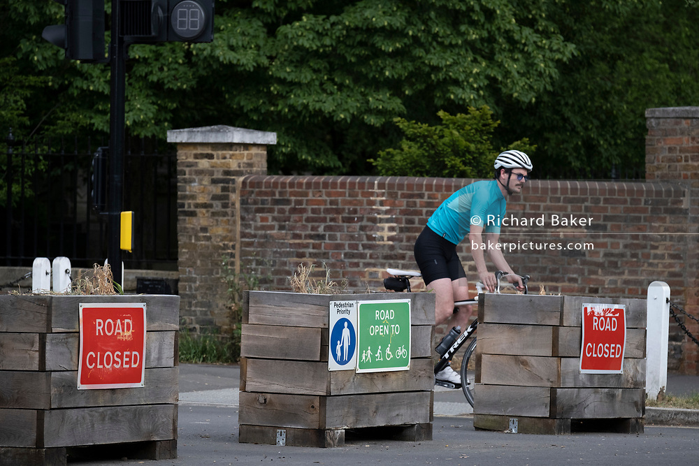 A cyclist passes through the barriers that form an LTN (Low Traffic Neighbourhood), an experimental closure by Southwark Council at the junction of Carlton Avenue and Dulwich Village restrictions also prevent traffic from passing through at morning and afternoon rush-hour times in the borough of Southwark, on 14th June 2021, in London, England.
