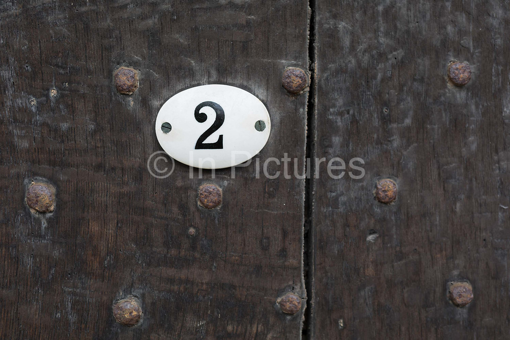 A detail of a number two and the rivets of an old wooden door in Ludlow, on 11th September 2018, in Ludlow, Shropshire, England UK.