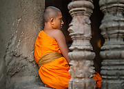 Young Buddhist monk in his orange robe at Angkor temple (Cambodia)