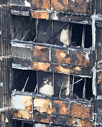 © Licensed to London News Pictures. 18/06/2017. London, UK. Burnt exterior panels and insulation are seen on Grenfell tower block. The blaze engulfed the 27-storey building killing dozens - with 34 people still in hospital, many of whom are in critical condition. The fire brigade say that they don't expect to find anyone else alive. Photo credit: Peter Macdiarmid/LNP