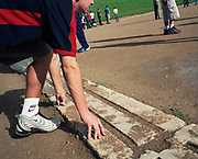 A tourist crouches on the original 4th century marble starting line at ancient Olympia's athletics track where both ancient Greeks and Romans held their games. Nike was the Goddess of Victory to whom Olympic athletes made offerings and prayers before competition. Hercules is said to have paced out the 600 Greek feet, or 'Stadion,' from which we get the word 'Stadium'. Olympic spectators suffered dehydration due to to extreme heat. The 29th modern Olympic circus came home to Greece in 2004 and at the birthplace of athletics and the Olympic ideal, amid the woodland of ancient Olympia where for 1,100 continuous years, the ancients held their pagan festival of sport and debauchery. The modern games share many characteristics with its ancient counterpart. Corruption, politics and cheating interfered then as it does now.