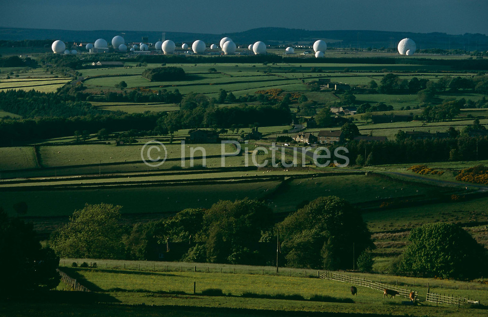 A view of the green Yorkshire moors countryside looking down from a nearby hill to the top secret intelligence-gathering base of RAF Menwith Hill, near Harrogate, Yorkshire, England. One sees the surreal-looking white radomes in the shape of golf balls - each containing a satellite dish - that are dotted across the science-fiction landscape. Many of these are used for signals interception from communications satellites and are commonly thought to be part of the ECHELON and PRISM eavesdropping projects by the NSA, a highly secretive world-wide signals intelligence and analysis network. Other parts of this notorious  site are thought to be used by the Space Based Infrared System employed by the US National Missile Defence program. The base has attracted significant levels of protest from anti-nuclear and pacifist groups.