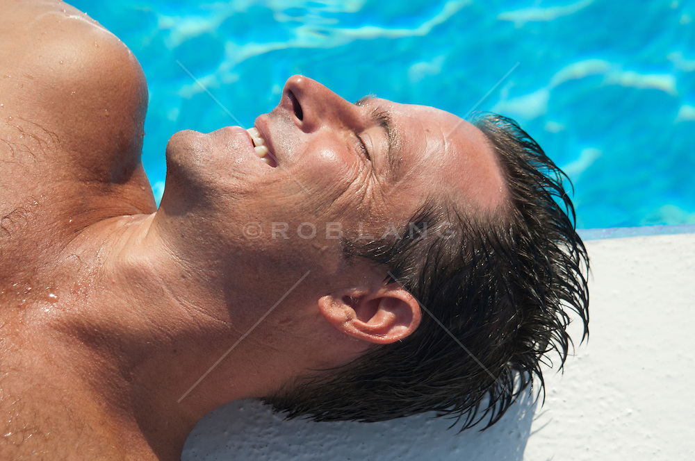 man with a big smile on his face as he rests in the sun by a swimming pool