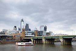 London City skyline, April 2019 UK. Cannon Street rail bridge in foreground