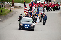 A Belmont Police cruiser and the Belmont Police Honor Guard escort members of the American Legion and the Belmont High School marching band towards Monument Square for Memorial Day ceremonies on Monday, May 29, 2017.  (Alan MacRae for the Laconia Daily Sun)