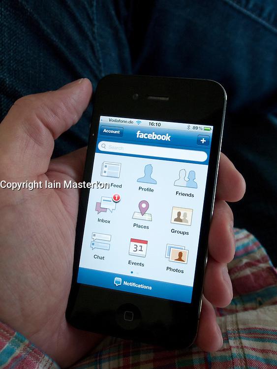 Man using Facebook app on an iPhone 4G smart phone