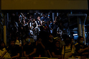 Local civilians watch protest from the stairs to the nearby station as police officers make massive arrest of protesters inside of bus on September 4th, 2019 in Hong Kong, China.