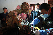 QUANZHOU, CHINA - JANUARY 10: (CHINA OUT) <br /> <br /> Workers clear the dust on monk Fuhou\'s body which was found not rotted after putting in a vat for three and a half years at Puzhao temple on Zimao Mountain on January 10, 2016 in Quanzhou, Fujian Province of China. 94-year-old monk Fuhou died in 2012 and his body was put by the sitting position into a vat with a cover for three and a half years. Monks found that Fuhou\'s body wasn\'t rotted on an opening vat rite on January 10 at Puzhao temple on Zimao Mountain in Quanzhou. The body would be cleaned and stuck with gold to be made into a golden Buddha. <br /> ©Exclusivepix Media