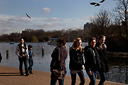 People gather to walk along the edge of The Serpentine in Hyde Park, London. This is a popular place for walking and other activities.