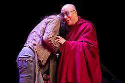 © Licensed to London News Pictures. 16/06/2012. Manchester , UK . The Dalai Lama hugs Russell Brand . Russell Brand introduces The Dalai Lama at the Manchester Arena , Greater Manchester , at the Stand Up and Be the Change youth event . The Dalai Lama is on a 10 day tour of the UK . Photo credit : Joel Goodman/LNP