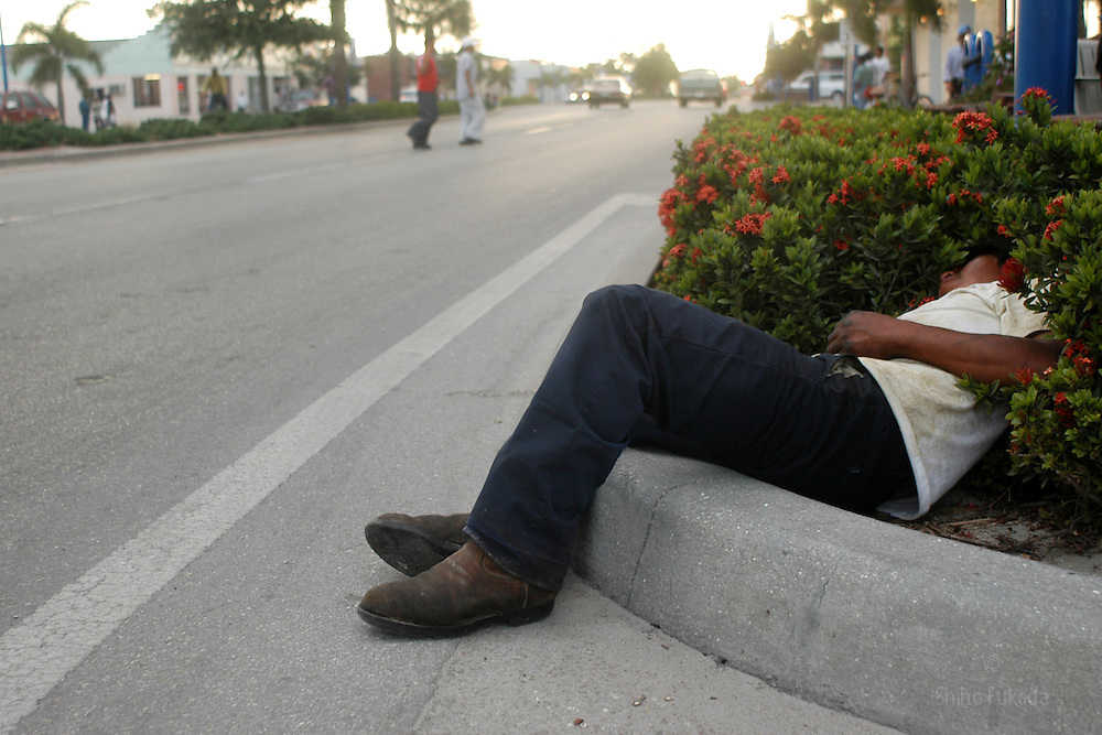 A migrant farm worker lays passed out on sidewalk in Immokalee, FL, Apr. 18, 2003.