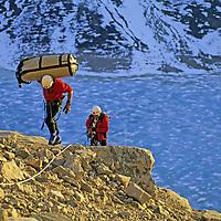 BAFFIN ISLAND, Nunavut, Canada. Alex Lowe & Greg Child (MR) haul heavy loads onto ledge on Great Sail Peak, above frozen lake in Stewart Valley.
