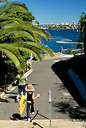 Mother and daughter (6 years old) strolling down path, with view across harbour to city. Taronga Zoo, Sydney, Australia