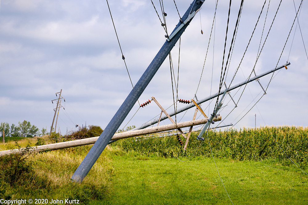 """12 AUGUST 2020 - HUXLEY, IOWA: Downed power poles and lines in central Iowa Wednesday, 48 hours after a wind storm tore through the area Monday. According to Iowa Governor Kim Reynolds, the storm damaged 10 million acres of corn and soybeans in Iowa, about 1 one-third of Iowa's 32 million acres of agricultural land. Justin Glisan, Iowa's state meteorologist, said the storm Monday, Aug. 10, lasted 14 hours and traveled 770 miles through the Midwest before losing strength in Ohio. The storm was a seldom seen """"derecho"""" that packed straight line winds of nearly 100MPH. The storm pummelled Midwestern states from Nebraska to Ohio.     PHOTO BY JACK KURTZ"""