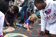 A young child and teenagers drawing on the road using colored chalk sending a message about peace reather than looting in the community. A peace street party was held in Clarence Road in Hackney, one of the worst hit streets in London during the London riots on Monday August 8th. The party was to gather the community and local police in a peaceful protest against the previous week's rioting and looting.