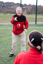 Trainer throwing and catching a tennis ball to a child on a playing field at their local leisure centre,