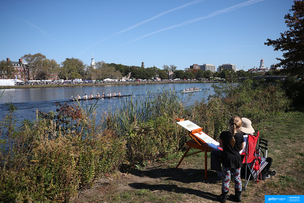 BOSTON, MASSACHUSETTS - OCTOBER 21: A  young girl shows curiosity as an artist works on the bank of the Charles river as crews take part in The 53rd Head of the Charles Regatta on the Charles River which separates Boston and Cambridge, Massachusetts, USA. The Head of Charles, which began in 1965, attracts over 11,000 athletes from around the globe. The course is 3 miles (4,800 meters) long and stretches from the start at Boston University's DeWolfe Boathouse near the Charles River Basin, passing Harvard University to the finish just after the Eliot Bridge. Boston, Massachusetts. 21st October 2017. (Photo by Tim Clayton/Corbis via Getty Images)