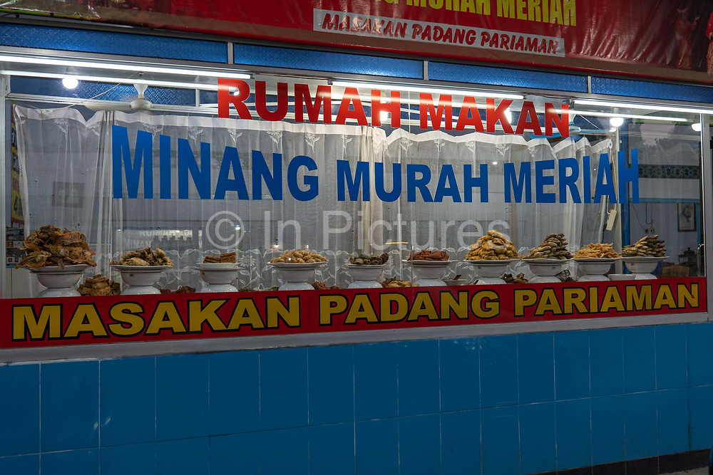 A window with traditional Indonesian restaurant selling Masakan Padang in Borobudur on the 25th October 2019 in Java in Indonesia.