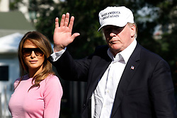 U.S. President Donald Trump waves as walks with First Lady Melania Trump on the South Lawn of the White House upon their return to Washington on July 1, 2018 from Bedminster, NJ. Photo by Yuri Gripas/UPI