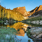 Reflections of Hallett Peak at sunrise in the calm waters of Dream Lake, Rocky Mountain National Park, Colorado.