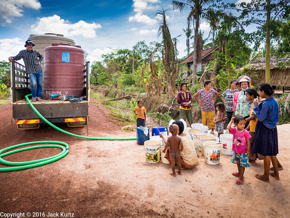 03 JUNE 2016 - SIEM REAP, CAMBODIA: A volunteer from Water on Wheels fills villagers water jugs at a water distribution point in Sot Nikum, a village northeast of Siem Reap. Wells in the village have been dry for more than three months because of the drought that is gripping most of Southeast Asia. People in the community rely on water they have to buy from water sellers or water brought in by NGOs. They were waiting for water brought in by truck from Siem Reap by Water on Wheels, a NGO in Siem Reap. Cambodia is in the second year of  a record shattering drought, brought on by climate change and the El Niño weather pattern. There is no water to irrigate the farm fields and many of the wells in the area have run dry.     PHOTO BY JACK KURTZ