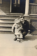 A father posing outside the porch with child