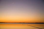 Orange sunset reflected on calm lake water.