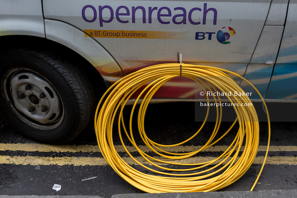 Detail of a BT Openreach van and a coil of yellow broadband fibre cable on the ground and awaiting insalation, on 16th February 2017, in the City of London, England.